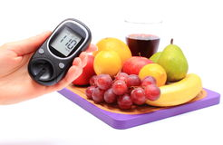 Hand of woman with glucometer and fresh fruits Stock Photography