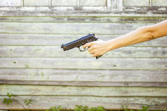 Hand of a woman with a gun isolated on a old wall background Stock Photography
