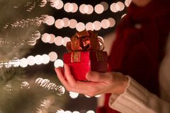 Hand woman hold red Christmas gift box on bokeh lights background.  Royalty Free Stock Images