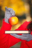 Hand of woman holding book and apple in autumn park Royalty Free Stock Photo