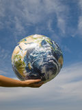 Hand of a woman holding earth. In front of blue sky Royalty Free Stock Images
