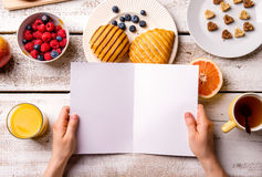 Hand of woman holding empty greeting card. Breakfast meal. Stock Images