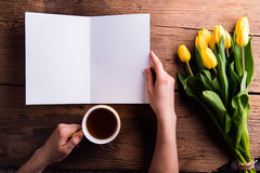 Hand of woman holding empty greeting card and coffee. Royalty Free Stock Image