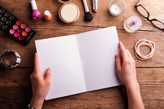 Hand of woman holding empty greeting card. Make-up products. Stock Photos