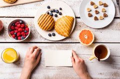 Hand of woman holding empty paper note. Breakfast meal. Stock Images