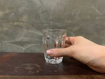 A hand of woman holding healthy mineral water in a clear glass on wooden table and cement wall, classic and vintage old st stock photography