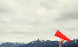 Hand of woman holding paper trumpet against natural landscape background Royalty Free Stock Photos