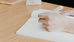 Hand of woman holding a pen for write to a book. Hand of working or student woman holding a pen for write a message to a book or notebook on a wood table Royalty Free Stock Photo
