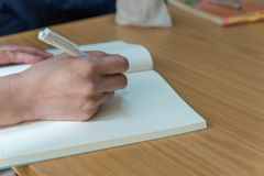 Hand of woman holding a pen for write to a book. Hand of working or student woman holding a pen for write a message to a book or notebook on a wood table Stock Photography
