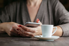 Hand woman holding phone and cup of coffee Stock Photo