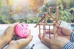 The hand of a woman holding a piggy bank and a coin in her hand and the hands of the men who are holding a model house under const royalty free stock image