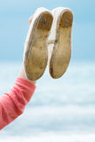 Hand of woman holding shoe. On the shoreline Stock Photos