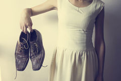 Hand of a woman holding shoes for men.  Royalty Free Stock Photography