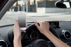 Hand of woman holding steering wheel and mobile phone driving car while texting distracted in risk. Close up hand of woman holding steering wheel and blank Royalty Free Stock Images