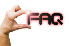 Hand of a woman is holding the write FAQ Stock Image