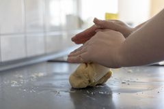 Hand of woman kneading dough for a cake on grey table royalty free stock images