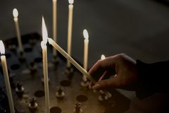 Hand of woman lighting candles in a church. Truth religion concept Royalty Free Stock Photo