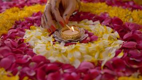 Hand of a woman lighting up a beautiful oil lamp placed in the center