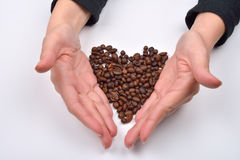 Hand of woman making shape of the heart from roasted coffee be Royalty Free Stock Photo