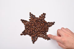 Hand of woman making a star symbol made from coffee beans on w Stock Photography