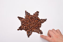 Hand of woman making a star symbol made from coffee beans on w Royalty Free Stock Images