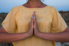 Hand of a woman meditating in a yoga pose on the beach at sunset.  Stock Photos