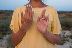 Hand of a woman meditating in a yoga pose on the beach at sunset.  Royalty Free Stock Photos