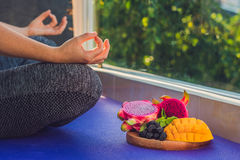 Hand of a woman meditating in a yoga pose, sitting in lotus with fruits in front of her dragon fruit, mango and mulberry royalty free stock photography