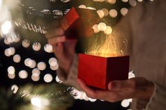 Hand of woman open red Christmas gift box with gold ray of magic light on bokeh lights background.  Royalty Free Stock Image