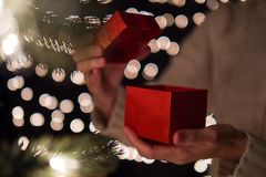 Hand woman opening Christmas gift box with bokeh lights background.  Royalty Free Stock Photo
