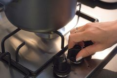 Hand woman opening gas burning from a kitchen gas stove. royalty free stock photography