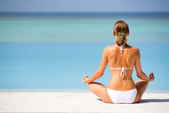 Hand of woman practices yoga and meditates on the beach. Maldives Stock Images