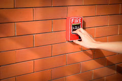 Hand of woman is pulling fire alarm on the brick wall Stock Photos