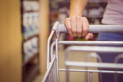 Hand of woman putting on trolley Stock Photos