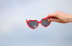 Hand of woman with red sunglasses shaped heart Royalty Free Stock Image