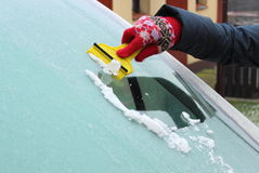 Hand of woman scraping ice from car windscreen Stock Images