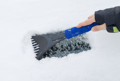 Hand of a woman Scraping snow and ice from the car windscreen Royalty Free Stock Photo