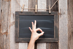 Hand of woman is showing Ok sign on chalkboard. royalty free stock photo