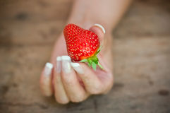 Hand of woman with strawberry  on wooden table background Stock Photo