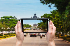 Hand woman taking phoot at victory Gate Patuxai, Vientiane, Laos Royalty Free Stock Photo