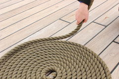 Hand of woman and thick rope wrapped in spiral lying on deck of ship Royalty Free Stock Images
