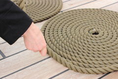 Hand of woman and thick rope wrapped in spiral lying on deck of ship Stock Photo