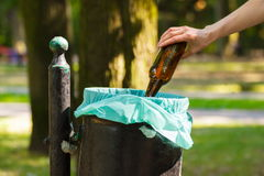 Hand of woman throwing glass bottle into recycling bin, littering of environmental Stock Photos