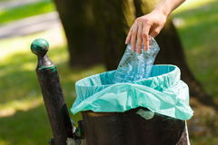 Hand of woman throwing plastic bottle into recycling bin, littering of environmental Royalty Free Stock Image