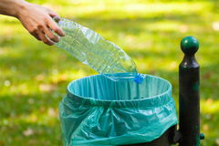 Hand of woman throwing plastic bottle into recycling bin, littering of environmental Royalty Free Stock Photos