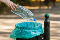 Hand of woman throwing plastic bottle into recycling bin, littering of environmental Royalty Free Stock Images