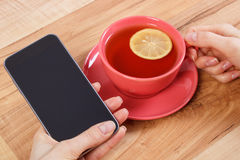Hand of woman touching blank screen of mobile phone, cup of tea Stock Image