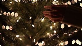 Hand woman touching Christmas tree with bokeh lights in Christmas time.  stock video