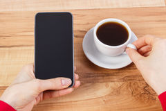 Hand of woman touching screen of mobile phone or smartphone, cup of coffee Stock Photo