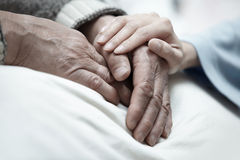 Care. Hand of woman touching senior man in clinic royalty free stock image